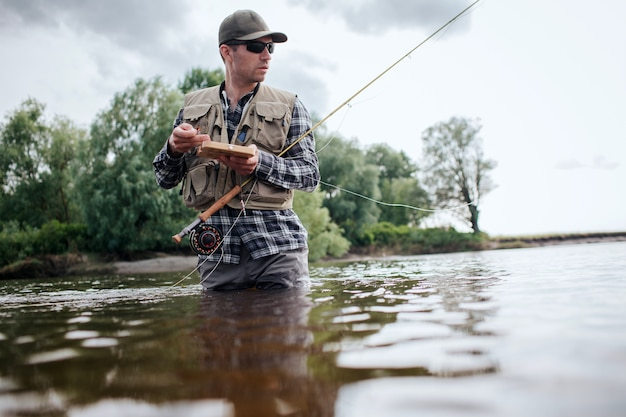 Man holding box with flies and plastic artificial baits. he is holding one of them in hand. also guy has a fly rod. he is holding it with another hand. man looks straigght forward.