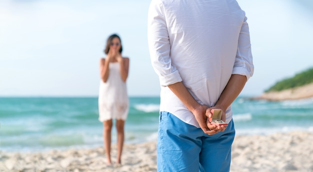 Man holding box with marriage ring making propose to his girlfriend at the beach