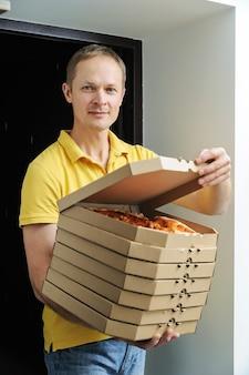 戸口にピザの箱を持って男