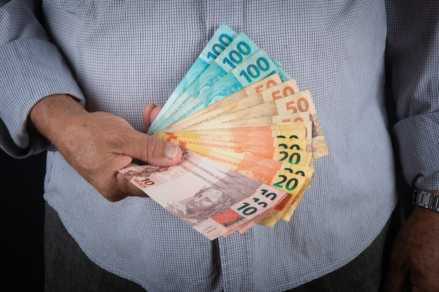 Man holding brazilian money banknotes