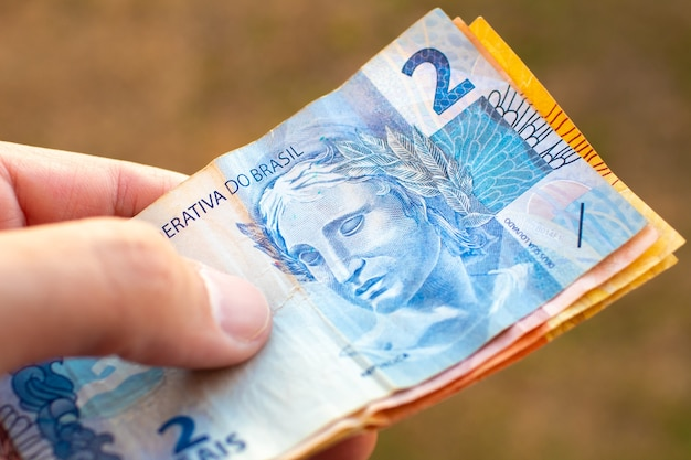 A man holding brazilian real bills