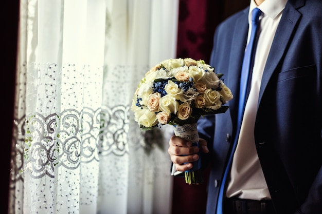 Man holding bridal bouquet in hands, groom getting ready in the morning before wedding ceremony