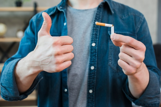 Мужчина держит сломанную сигарету и показывает большой палец вверх жест