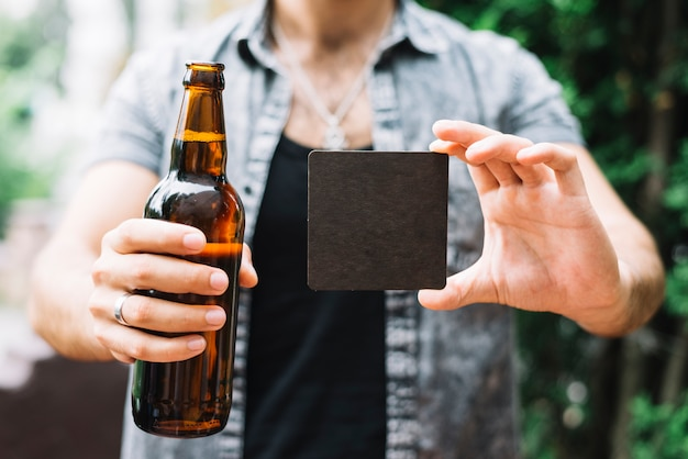 Man holding brown beer bottle and black blank card in hands