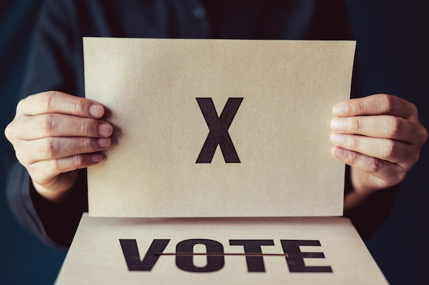 Man holding brown paper with x mark above vote box