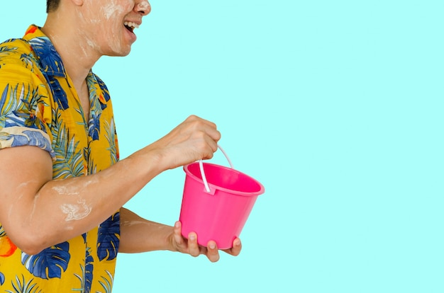Man holding bucket for water festival in thailand.