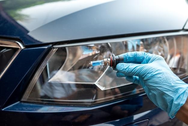 Man holding bulb for repair car light, headlight