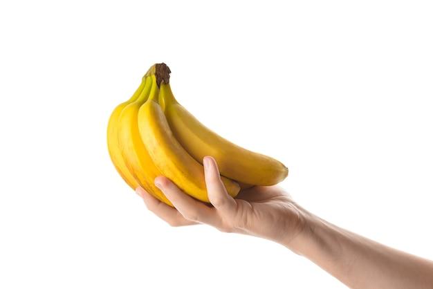 Мужчина держит в руке кучу бананов. изолированные на белом фоне.