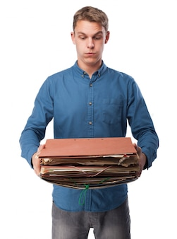 Man holding a bunch of work folders