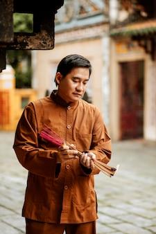 お寺でお香の束を持っている男