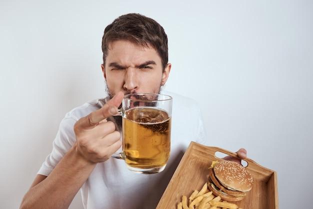 Мужчина держит гамбургер, картофель и пиво