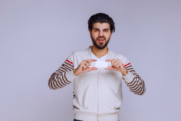 Man holding a business card and presenting or recieving it.