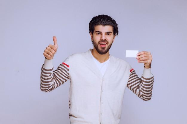 Uomo che tiene un biglietto da visita e che mostra il pollice sul segno.