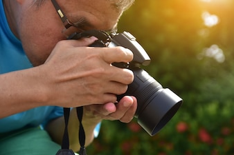 Man holding camera and green leaf nature background