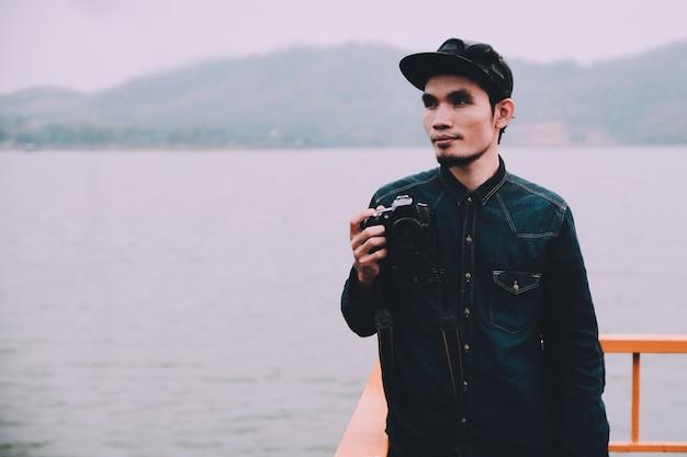 手にカメラを持ち、海に立っている男