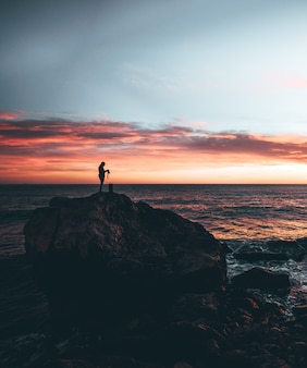 Man holding a camera in the top of a rock with a sunset