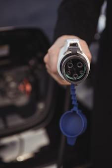 Человек, держащий автомобильное зарядное устройство на станции зарядки электромобилей