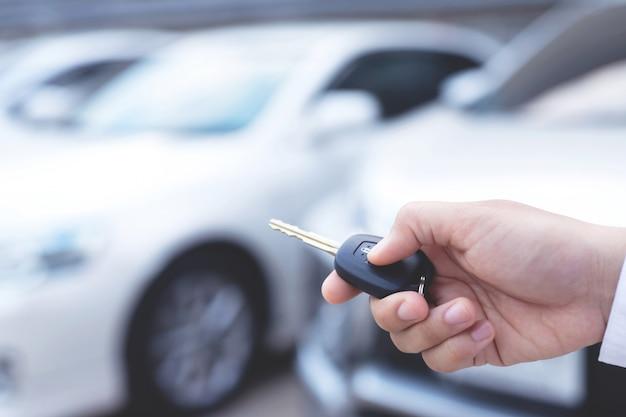 Мужчина держит ключ от машины и нажимает его на парковке