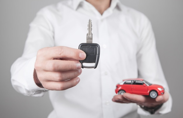 Man holding car key with car in office.