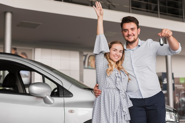 Мужчина держит ключи от машины и женщина поднимает руку