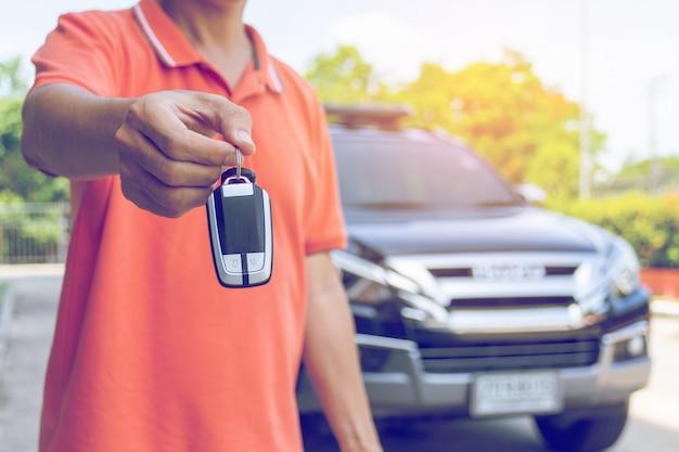 Man holding car keys with car