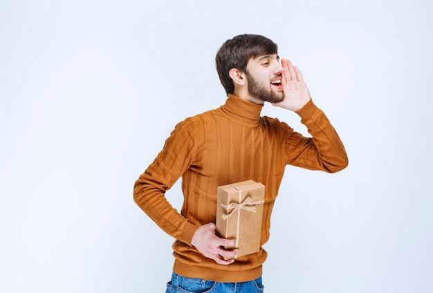 Uomo che tiene una scatola regalo di cartone e chiama qualcuno sul lato destro.