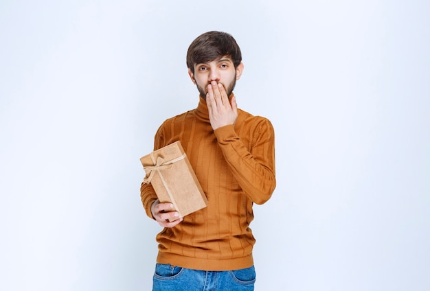 Man holding a cardboard gift box and looks confused and hesitating.