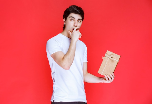 Man holding a cardboard gift box and looks confused.