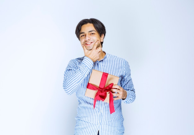 Man holding a cardboard gift box with red ribbon and hesitating or embarassed. high quality photo