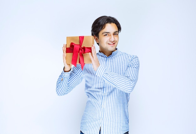Man holding a cardboard gift box with red ribbon. high quality photo