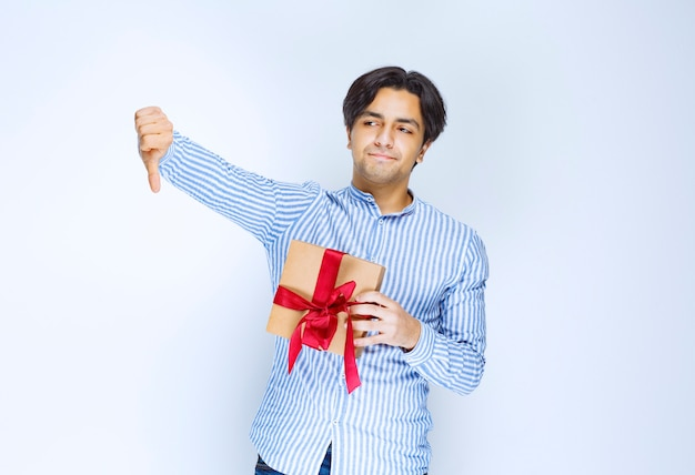 Man holding a cardboard gift box with red ribbon and showing dislike sign. high quality photo