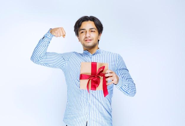 Uomo che tiene una scatola regalo di cartone con un nastro rosso e mostra il pugno come una persona di successo. foto di alta qualità