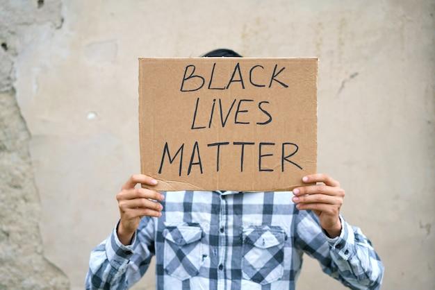 Мужчина держит картон с надписью черная жизнь имеет значение кавказский парень с демонстрацией плаката ...