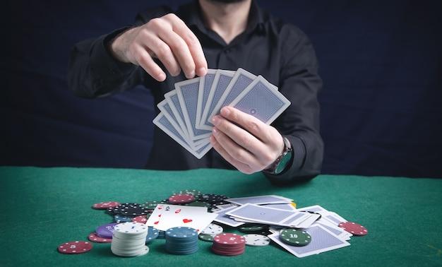 녹색 테이블에 카지노 칩이 있는 카드를 들고 있는 남자.