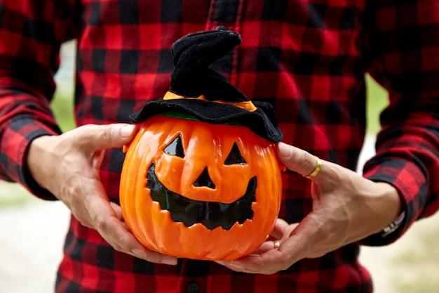 Man holding carved pumpkin.