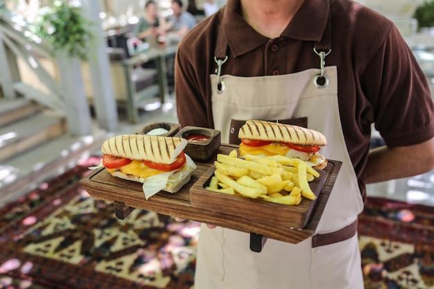 Мужчина держит куриные бутерброды с картофелем фри