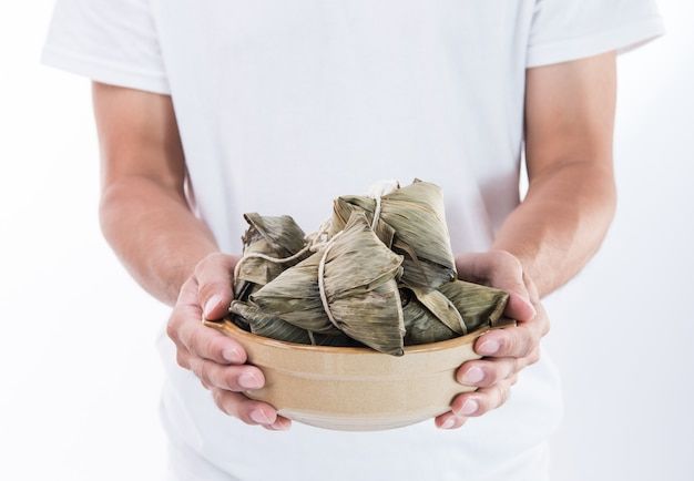 드래곤 보트 축제 음식에 대한 중국 전통 zongzi 쌀 만두를 들고 남자