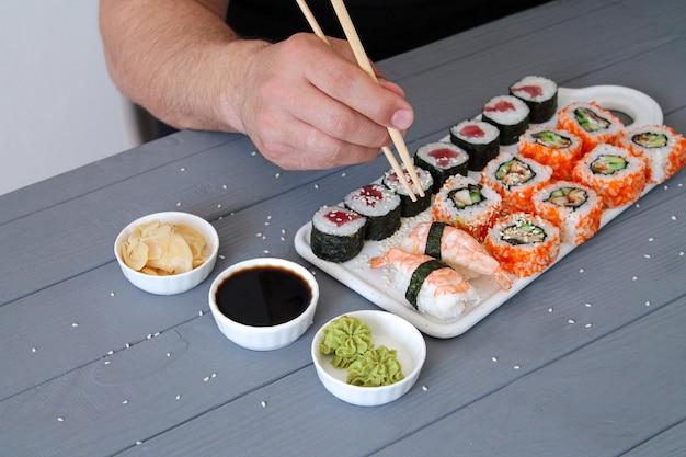 Мужчина держит палочки и ест суши в ресторане