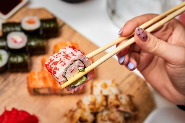 Человек, держащий суши-роллы палочками на фоне набора различных суши-роллов
