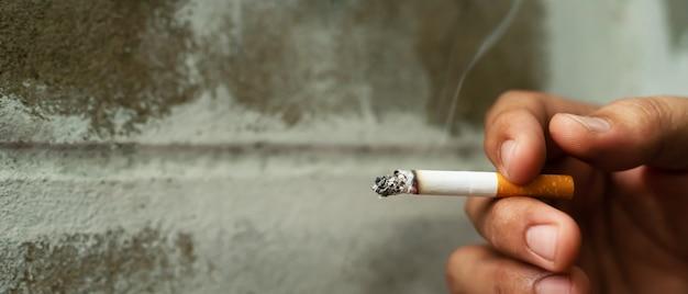 Мужчина держит сигарету в руке и курит
