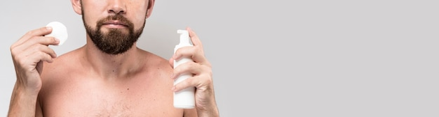 Man holding a cleansing disk and shaving cream bottle