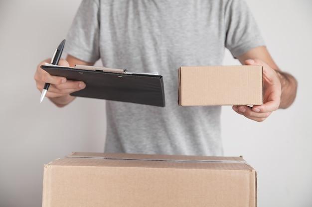 クリップボードと段ボール箱を持っている男。製品、コマース、小売、配送