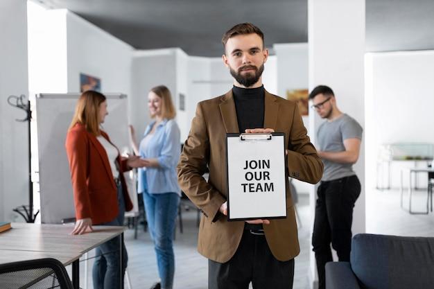 L'uomo in possesso di un blocco appunti al lavoro con unirsi al nostro messaggio di squadra