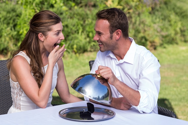Man holding cloche while proposing woman