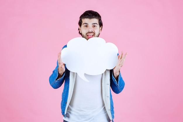 Uomo che tiene un fumetto vuoto a forma di nuvola e si diverte.