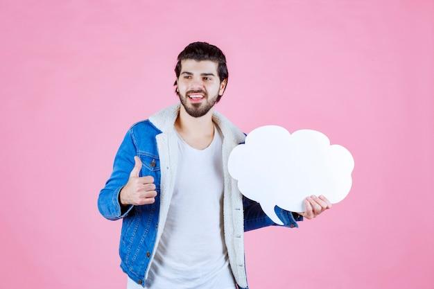 Uomo che tiene una lavagna vuota a forma di nuvola e si sente un vincitore a