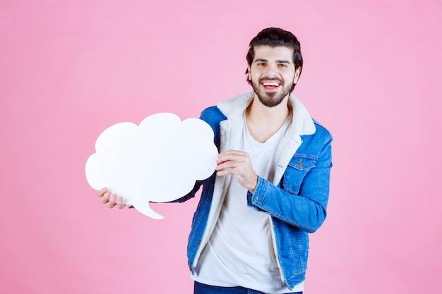 Uomo che tiene una lavagna vuota a forma di nuvola e si diverte