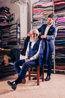 Man holding coat over his senior man's shoulder in the shop