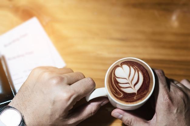 男持株コーヒーカップと搭乗券を飛行機で飛行旅行を待っています。