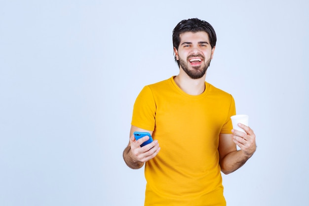 Man holding a coffee cup and demonstrating his new model smartphone.